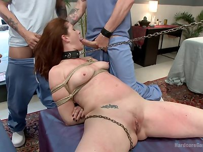 Redhead gets gagged by dicks while sitting tied up in trammels
